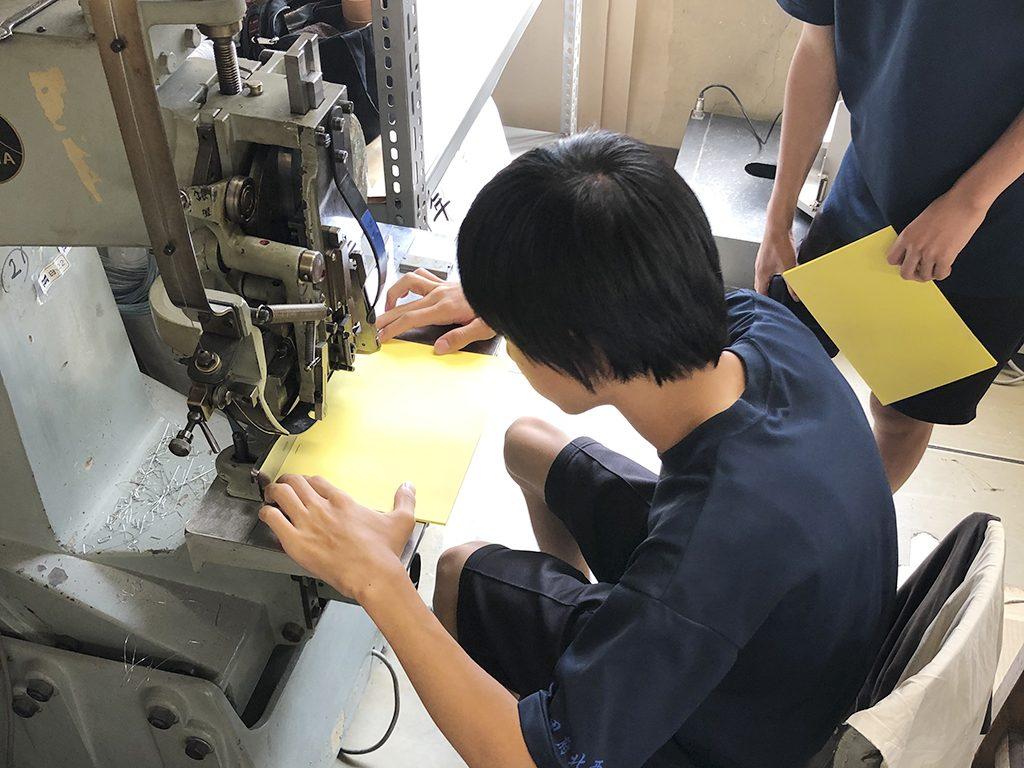 インターンの中学生が、中綴じ機を体験する写真です。